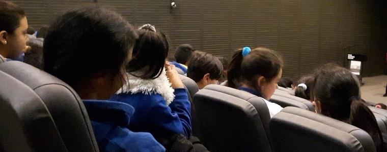 Fotografía de butacas de cine ocupadas por niños y niñas. La fotografía fue tomada desde atrás, por lo que solo se ve el pelo y parte de sus perfiles.